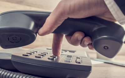Closeup of businessman making a telephone call by dialing a phone number on a classical black landline device with a retro faded look.